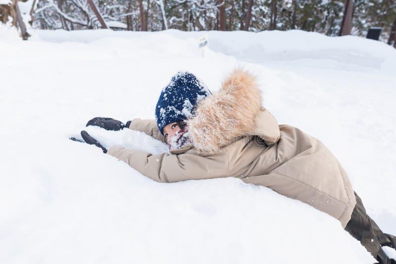 Asiatisk pojke som spelar snö fotografering för bildbyråer
