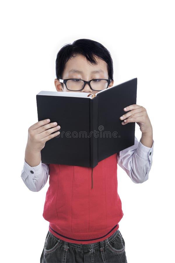 Asiatisk pojkeläsebok - som isoleras på vit royaltyfri foto