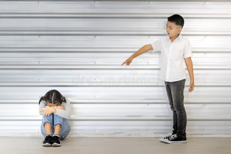 Asiatisk pojkepunkt på att sitta den asiatiska flickan, vit vägg bak dem royaltyfri foto