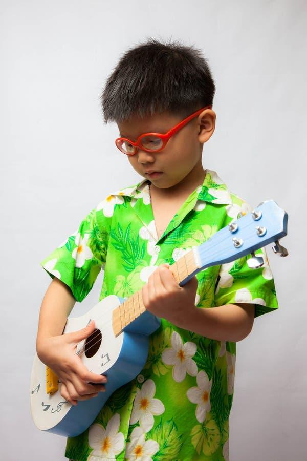 Asiatisk pys som spelar ukulelet arkivbild