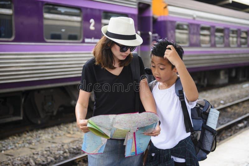 Asiatisk ryggsäckhandelsresandekvinna med den gulliga sonen som använder den generiska lokala översikten på en drevstation fotografering för bildbyråer