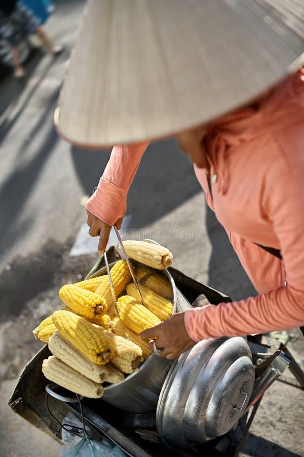 Asiatisk säljare i den traditionella koniska hatten som säljer kokt majs fotografering för bildbyråer