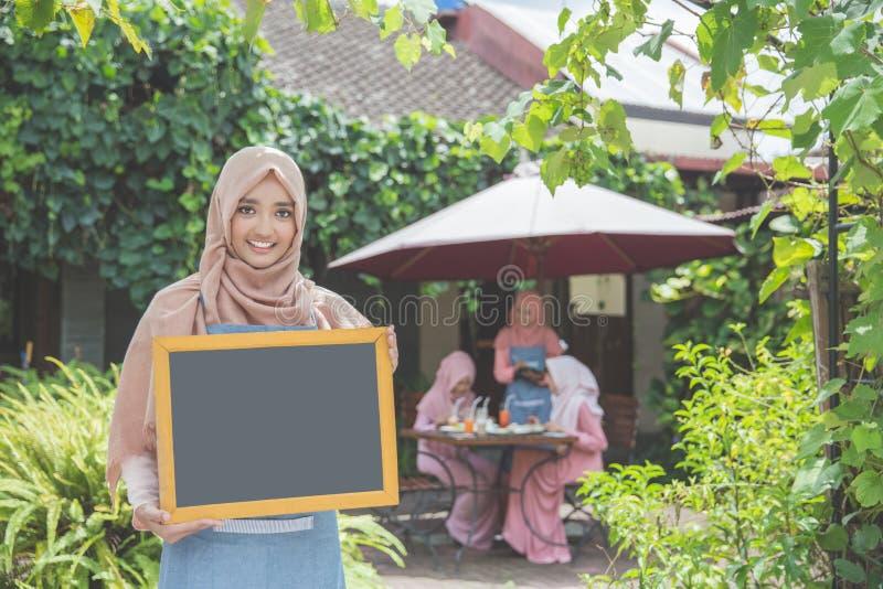 Asiatisk servitris som framme står av en tom cha för kafé och för innehav royaltyfri foto