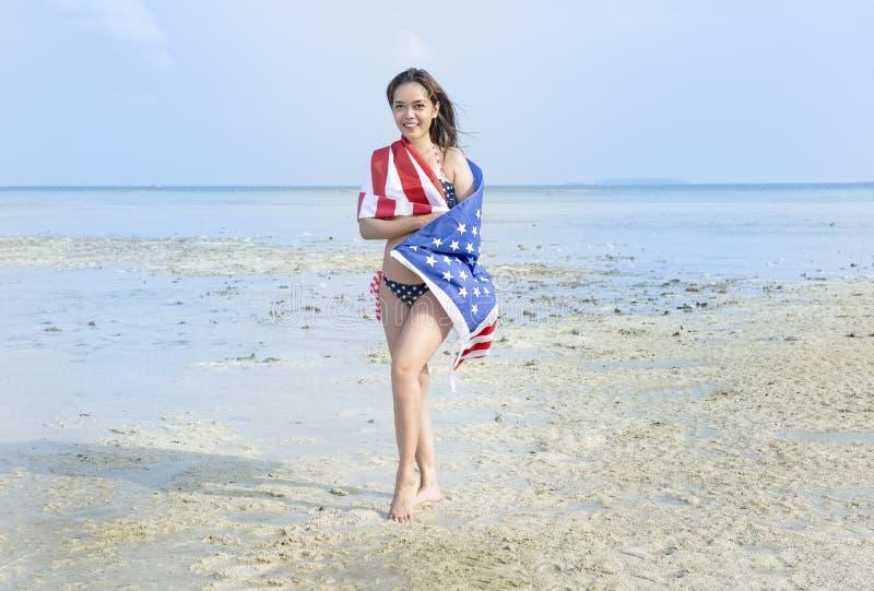 Asiatisk sexig flicka i bikinin av amerikanska flaggan som täcker hennes kropp med amerikanska flaggan på stranden royaltyfri bild