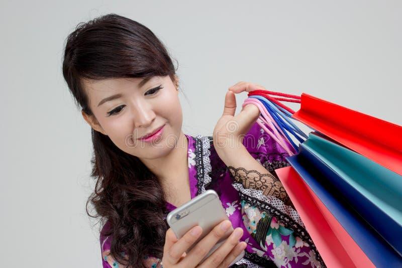 Asiatisk shoppingkvinna som använder den smarta telefonen royaltyfria bilder