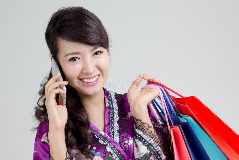 Asiatisk shoppingkvinna som använder den smarta telefonen fotografering för bildbyråer