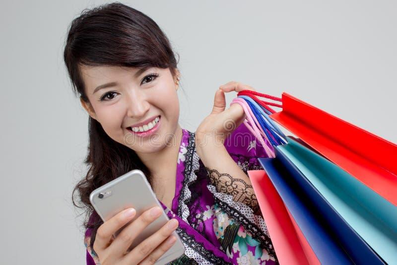 Asiatisk shoppingkvinna som använder smarta färgrika shoppingpåsar för telefon och för innehav royaltyfria foton