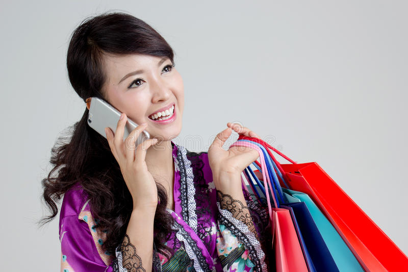 Asiatisk shoppingkvinna som använder smarta färgrika shoppingpåsar för telefon och för innehav fotografering för bildbyråer