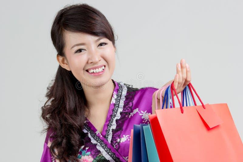 Asiatisk shoppingkvinna som rymmer färgrika shoppingpåsar royaltyfri bild