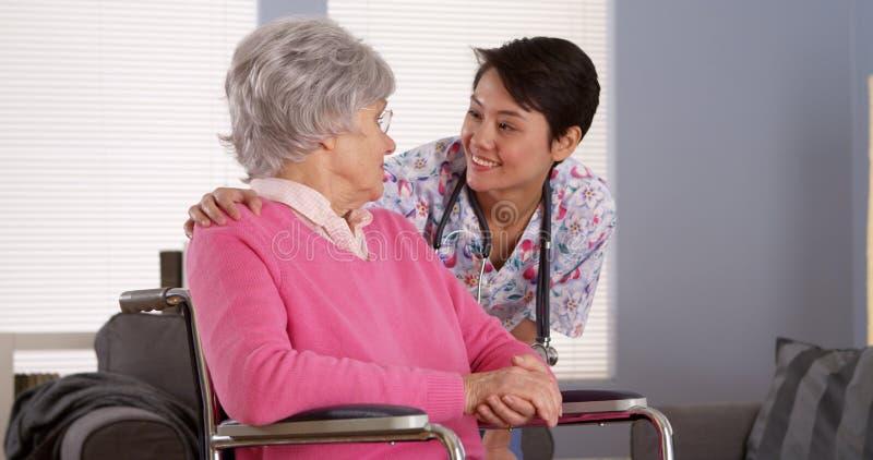 Asiatisk sjuksköterska som talar med den höga patienten arkivbilder