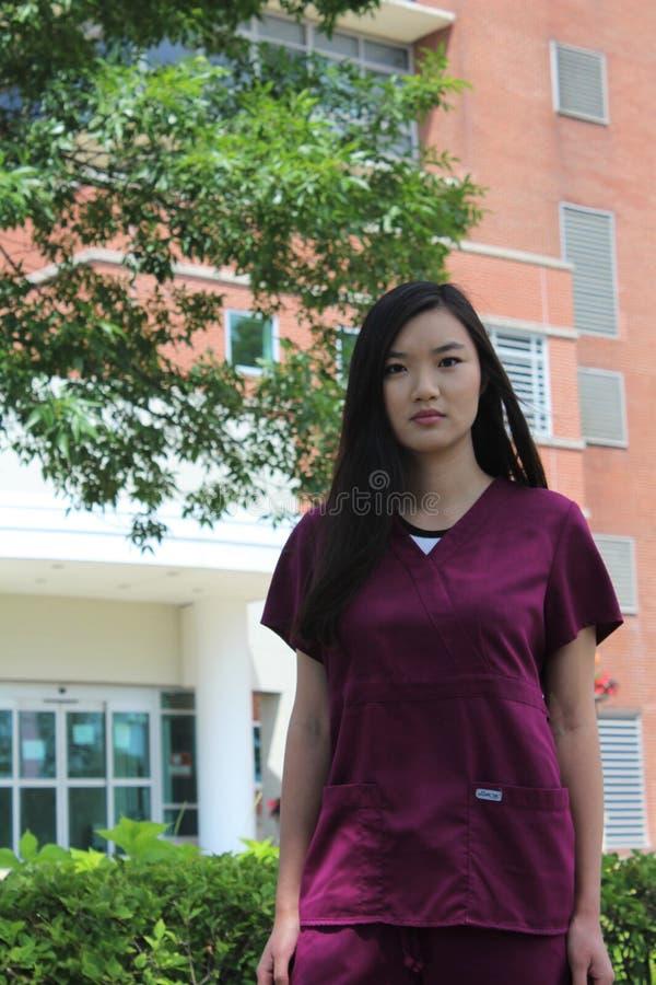Asiatisk sjuksköterska Wearing Scrubs Stands framme av sjukhuset arkivbild