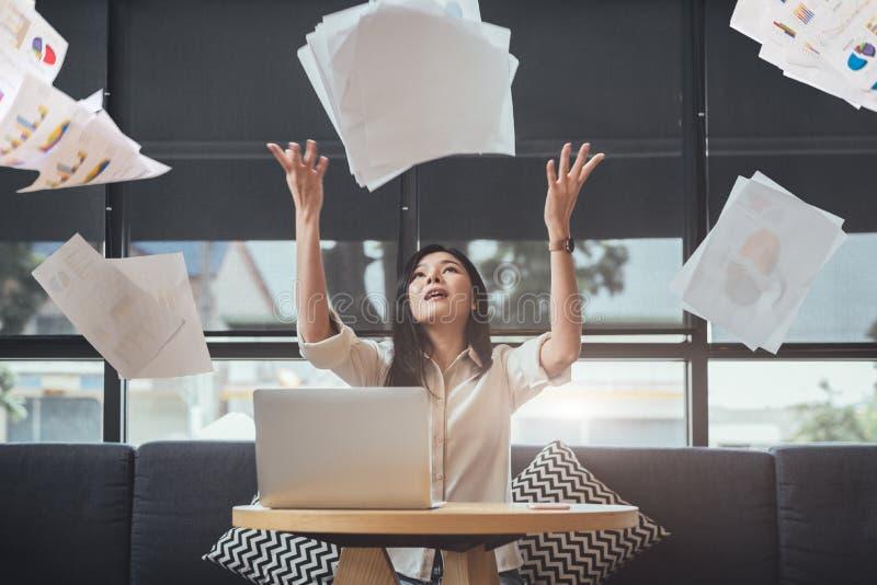 Asiatisk skönhetaffärskvinna som kastar skrivbordsarbete in i luften lyckad och prestationbegrepp Affärs- och ockupationbegrepp fotografering för bildbyråer