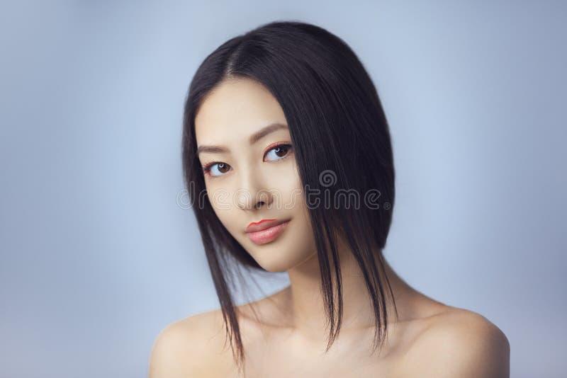 Asiatisk skönhetkvinna med idérikt smink Det lyckliga ung flickainnehav hänger lös på en vitbakgrund le för flicka arkivfoto