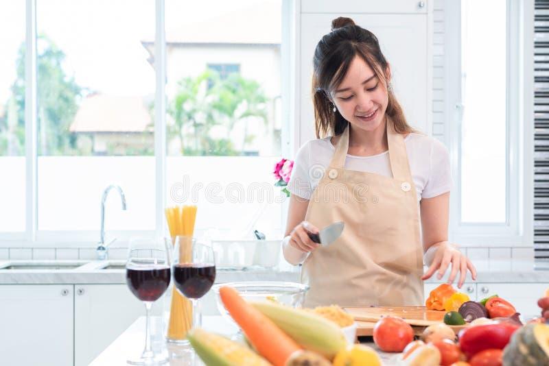 Asiatisk skönhetkvinna som lagar mat och skivar grönsaken i kökrum royaltyfri fotografi