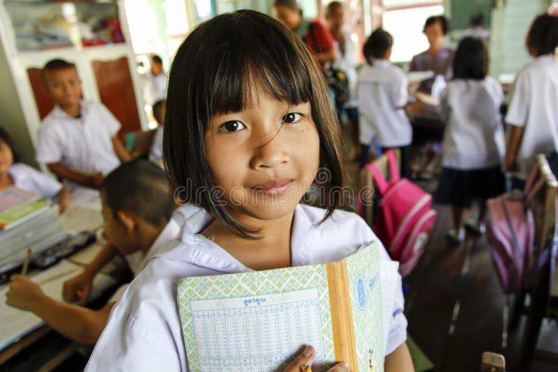 Asiatisk skolaflicka i enhetlig håll en anmärkningsbok i hennes arm arkivfoton