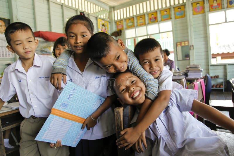 Asiatisk skolagrupp i likformign som spelar med kameran arkivbilder