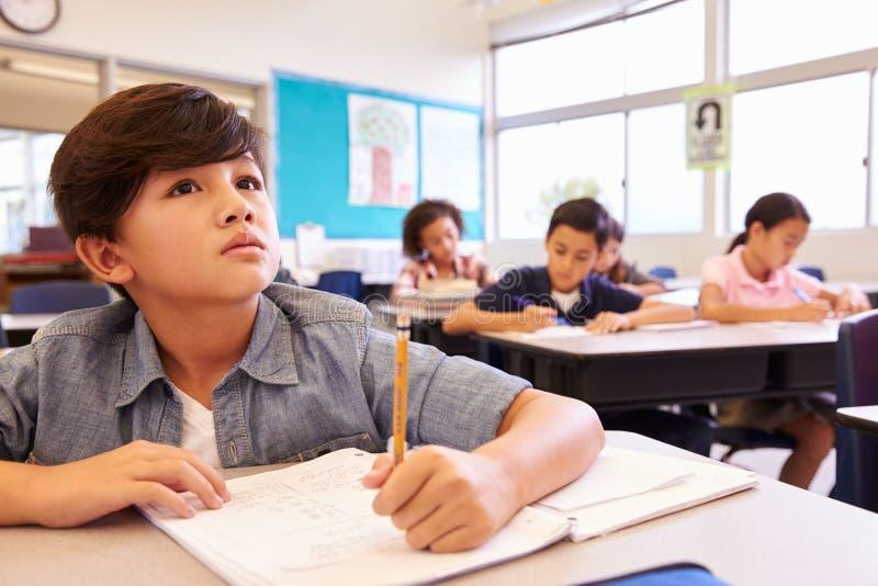 Asiatisk skolpojke i grundskolagrupp som ser brädet royaltyfria bilder