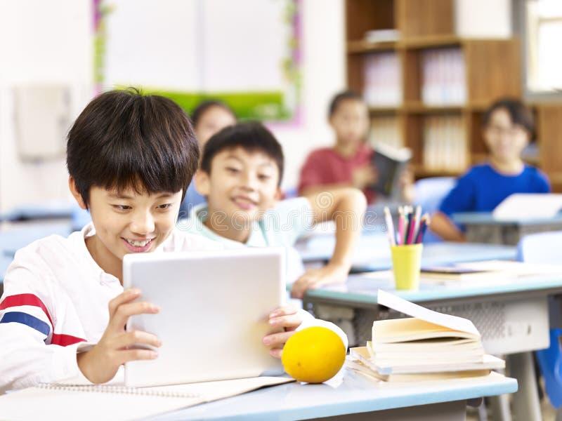 Asiatisk skolpojke som använder minnestavlan i klassrum arkivbild