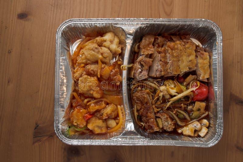 Asiatisk snabbmat från hemsändning i en folie på en trätabl arkivfoton