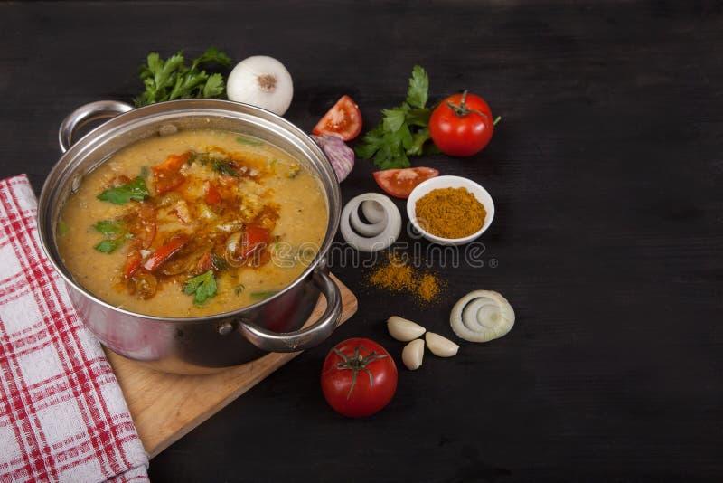Asiatisk soppa för röd lins i en panna på en svart träbakgrund Lökar, vitlök, tomater och kryddor royaltyfria foton