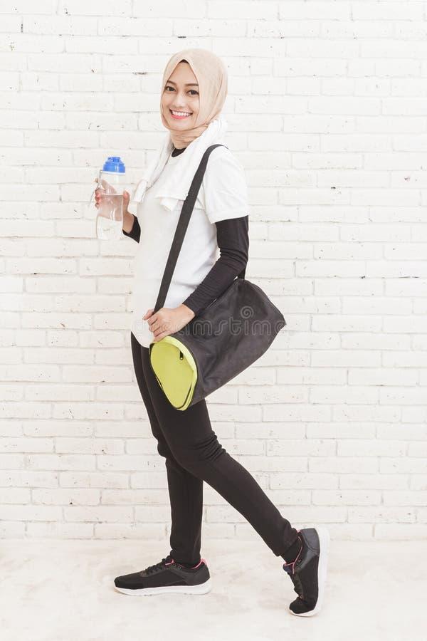 Asiatisk sportig kvinna som går, medan bärande sportar hänger löst anf en bottl arkivbild