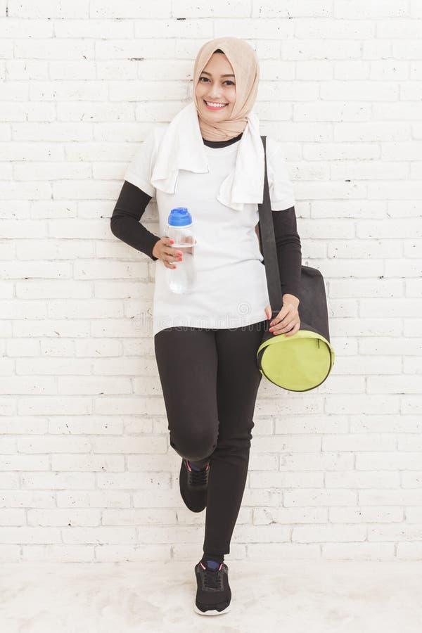 Asiatisk sportig kvinnabenägenhet mot väggen som vilar efter workou arkivbild