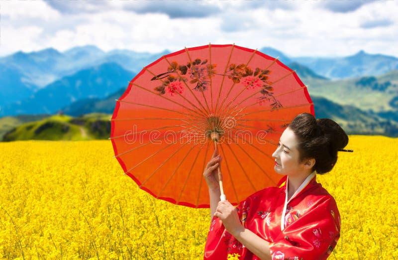 Asiatisk stilstående av en kvinna med det röda paraplyet royaltyfri fotografi