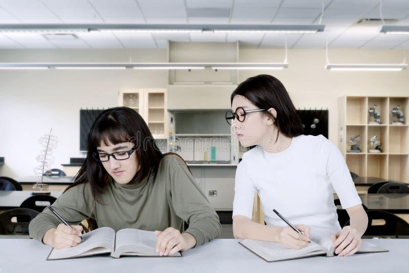 Asiatisk student som kikar hennes klasskompis i klassrumet arkivfoton