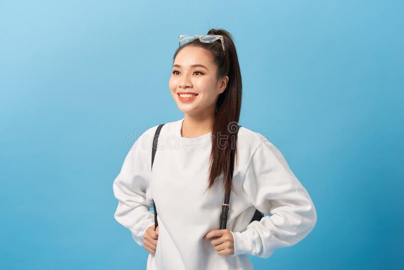 Asiatisk studentflicka över den lyckliga isolerade blåa väggen och att le arkivfoton