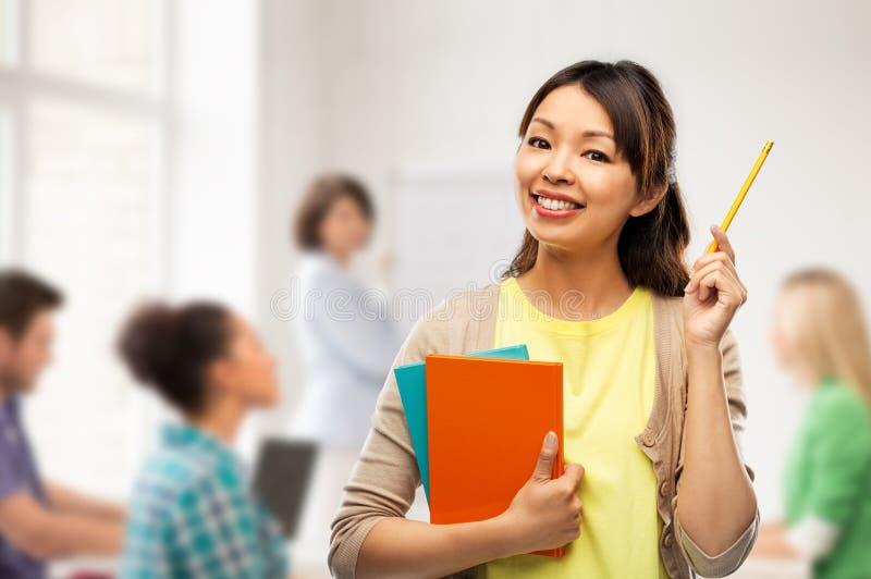 Asiatisk studentkvinna med böcker och blyertspennan arkivbild