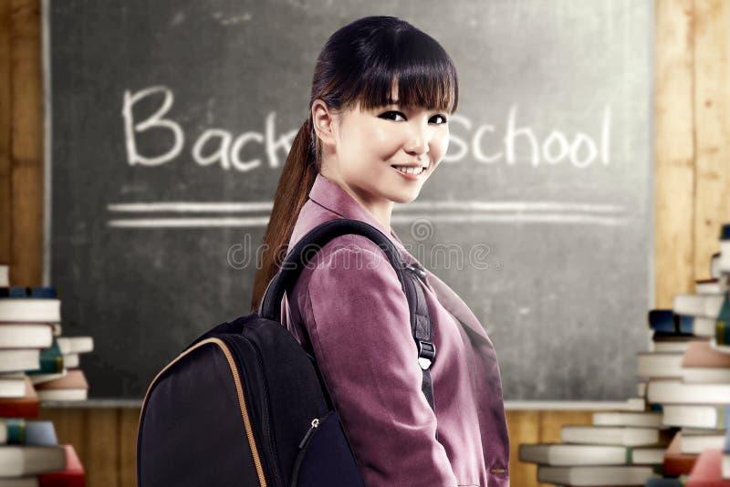 Asiatisk studentkvinna med ryggsäckanseende och att se tillbaka i klassrumet med högar av böcker och svart tavla royaltyfri foto