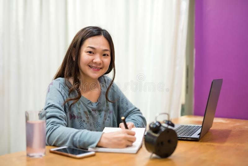 Asiatisk studentläsning och att ta anmärkningen i bok arkivbild