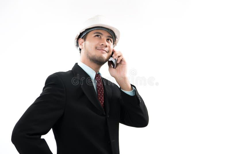 Asiatisk tekniker eller arkitekt som ler och använder en mobiltelefon royaltyfri bild