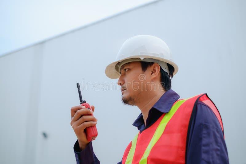 Asiatisk tekniker i säkerhetslikformig och vithjälm genom att använda walkie-talkie på suddig branschväxtbakgrund fotografering för bildbyråer