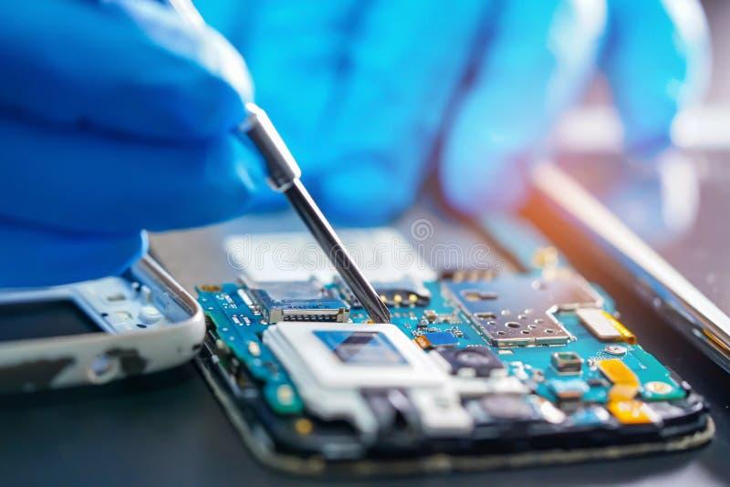 Asiatisk tekniker som reparerar det huvudsakliga brädet för mikroströmkrets av elektronisk teknologi för smartphone arkivfoto