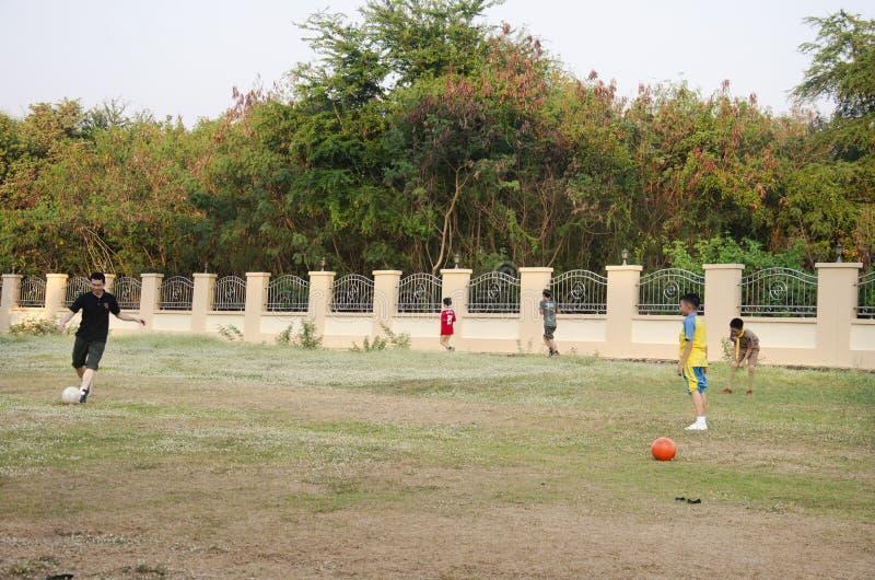 Asiatisk thai faderutbildning och spelafotboll eller fotboll med sonen på lekplatsen på trädgård för gård parkerar offentligt i T royaltyfri bild