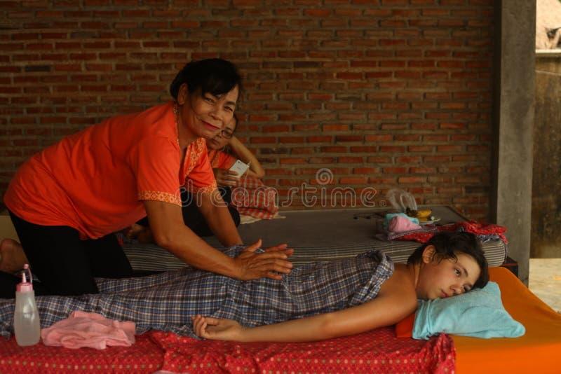 Asiatisk thai kvinna som utför massage till den europeiska tonåringpojken royaltyfri fotografi