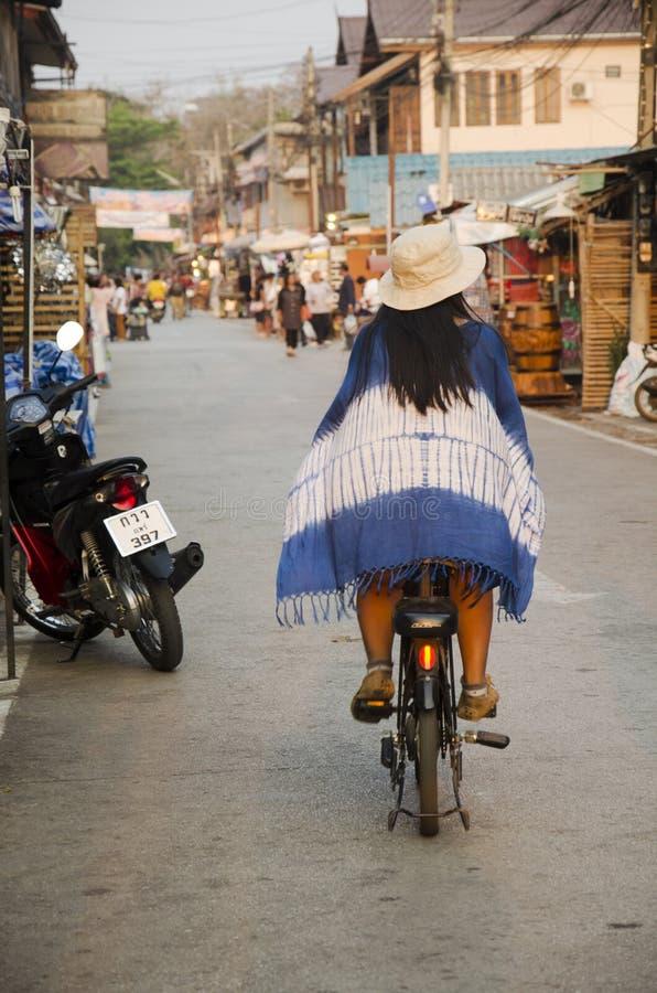 Asiatisk thai kvinnarittcykel på gatanattmarknad i liten gränd på Chiang Khan arkivbilder