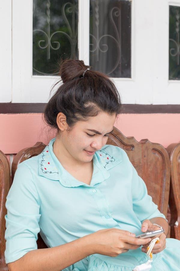 Asiatisk thailändsk kvinna som använder den smarta telefonen royaltyfria bilder