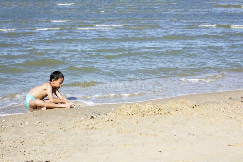 Asiatisk thailändsk pojke som spelar sand arkivfoto