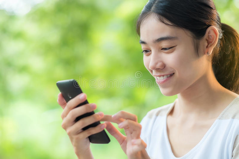 Asiatisk tonårig kvinna som använder smartphonen arkivbild