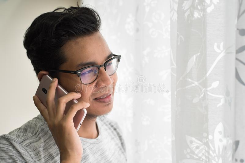 Asiatisk tonårig talande ho hans smartphone i hans hem arkivfoton