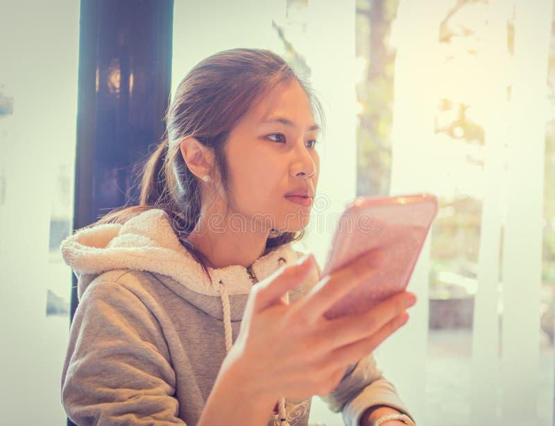 Asiatisk tonåring som använder mobiltelefonen arkivfoton