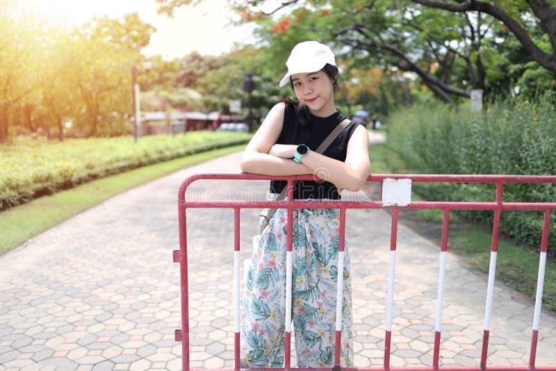 Asiatisk tonåringflicka som bär en hattställning för att ta bilder arkivbilder