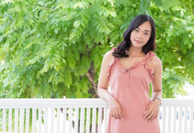 Asiatisk tonårs- flicka för trevligt leende på balkong arkivfoto
