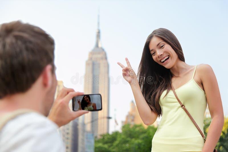 Asiatisk turist för NYC som poserar på Empire State Building royaltyfri bild