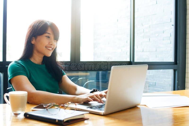 Asiatisk ung ägareaffärskvinna som direktanslutet arbetar och att kontrollera post på process för bärbar datoruppläggningarbete i arkivfoto