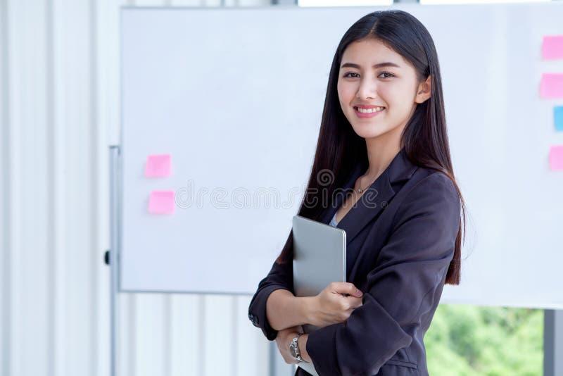 asiatisk ung affärskvinna som rymmer isola för Digital minnestavladator royaltyfri fotografi