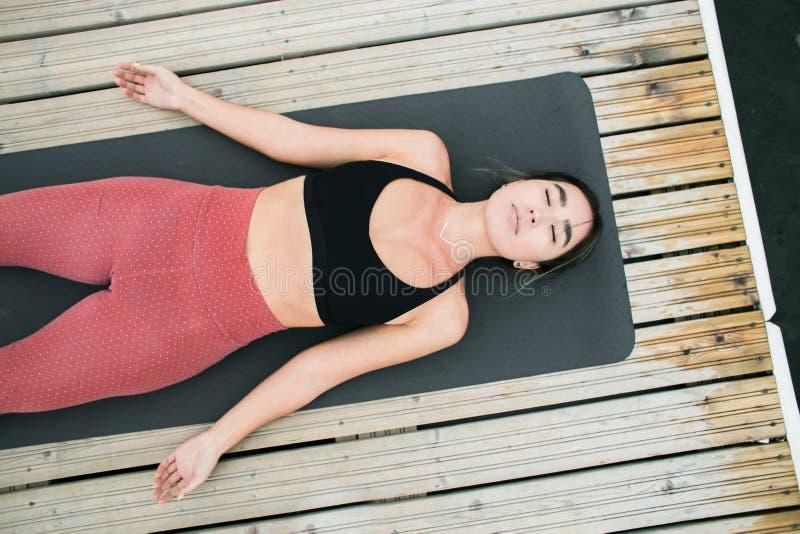 Asiatisk ung flicka som utomhus gör yoga på pir vid sjön royaltyfri fotografi
