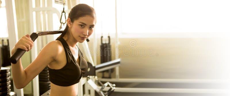 asiatisk ung konditionkvinna i sportswear som övar byggande muskler med maskinkabelövergång i ligth för sportidrottshallmorgon arkivbilder